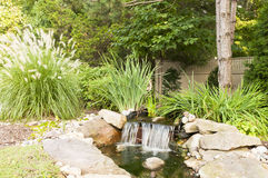 Backyard landscaped waterfall. A quiet, decorative, landscaped waterfall in the backyard of a private home Stock Photos
