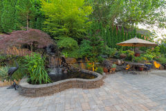 Backyard Landscaping Patio with Waterfall Pond. Backyard Garden landscaping with waterfall pond trees plants trellis decor furniture brick pavers patio hardscape Royalty Free Stock Image