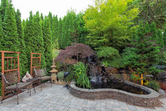 Backyard Landscaping with Waterfall Pond. Backyard Garden landscaping with waterfall pond trees plants trellis decor patio furniture brick pavers Royalty Free Stock Images