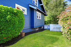 Backyard with lawn and white wooden fence Stock Images