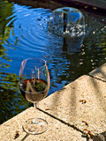 Backyard party. Glass of red wine on the edge of a backyard pond Royalty Free Stock Photography