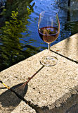 Backyard party. Glass of red wine on the edge of a backyard pond Royalty Free Stock Photos
