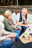 Backyard Party at Full Speed. Profile view of pretty elderly women holding glass of red whine in hand while entertaining her guests with small talk, they royalty free stock photos