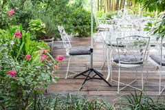 Backyard patio area with alloy table. And chairs on a wooden terrace stock photo