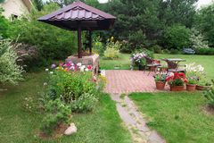 Backyard Patio Area with Fireplace and Furniture. Green Party area. Barbecu e Area. Stone stock images