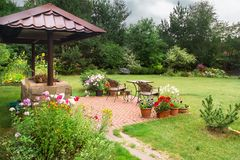 Backyard Patio Area with Fireplace and Furniture. Green Party area. Barbecu e Area. Stone stock photography