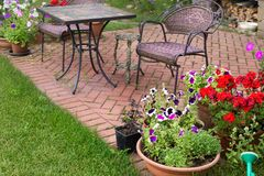 Backyard Patio Area with garden Furniture and Flowers. Backyard Patio Area with Fireplace and Furniture. Green Party area. Blooming Flowers and Green Grass stock images