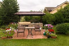 Backyard Patio Area with Stone Fireplace. Backyard Patio Area with Fireplace and Furniture. Green Party area. Barbecue Area. Stone.Blooming Flowers royalty free stock photo