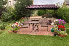 Backyard Patio Area with Stone Fireplace. Backyard Patio Area with Fireplace and Furniture. Green Party area. Barbecue Area. Stone.Blooming Flowers stock photos