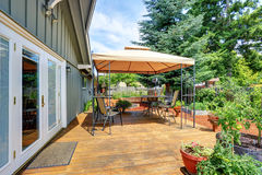 Backyard patio area with table set and opened orange umbrella Stock Images