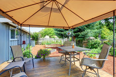 Backyard patio area with table set and opened orange umbrella Royalty Free Stock Photo