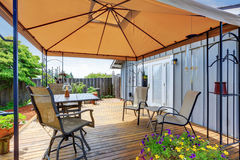 Backyard patio area with table set and opened orange umbrella Royalty Free Stock Images
