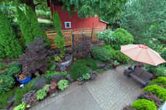 Backyard Patio Landscaping with Red Barn Overview. Backyard garden landscaping with paver bricks patio hardscape trees potted plants shrubs pond rocks furniture Royalty Free Stock Photography