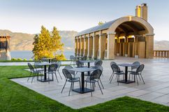 Backyard Patio with Metal Table and Chairs. Empty Metal Tables in a Backyard Patio with a Breathtaking View of a Lake at Sunset royalty free stock photography