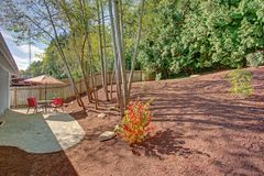 Backyard Patio With Red Striped Umbrella royalty free stock images