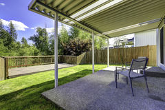 Backyard patio with walkout deck. Backyard patio with concrete floor and wooden walkout deck with railings royalty free stock photo