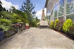 Backyard Paver Patio with Garden Accessories. Garden Backyard Paver Patio with Chairs Umbrella Plants Pots Trees and Decoration royalty free stock photography