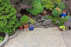 Backyard Paver Patio Landscaping Overview. Backyard garden landscaping with paver bricks patio hardscape trees potted plants shrubs pond rocks and decor Royalty Free Stock Photo