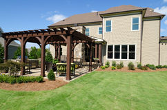 Backyard with pergola. A large house with landscaped backyard and pergola Stock Photo