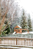 Backyard Playground and Fence in Snow royalty free stock photography