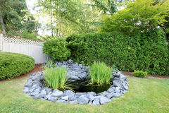 Backyard pond with grey rocks and green fenced yard. Royalty Free Stock Photo