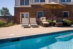 Backyard Pool with seats and umbrella. Swimming pool with relaxing seats and sun umbrella providing shade stock photos