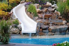 Backyard pool and slide. A backyard landscape with a swimming pool and a slide off of the rock waterfall royalty free stock image