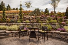 Modern Stone terraced luxury yard. A small table sits ready for use in a beautifully designed backyard with stone and plant accents Royalty Free Stock Images