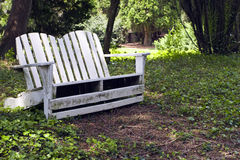 Backyard Retreat. Relaxing backyard retreat featuring a white wooden seat surrounded by trees and plant life. Sitting in the cool shade Stock Photo