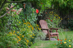 Backyard Retreat. A weathered wood chair sits at the end of a stone walkway, hidden behind colorful zinnias Royalty Free Stock Photos