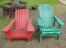 Backyard rustic wooden chairs in red and green royalty free stock photos