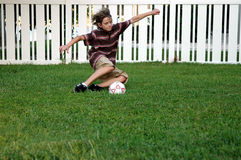 Backyard soccer. A boy playing soccer in the backyard royalty free stock images