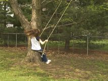 Backyard Swing. A child swings on an old fashioned tree swing in the backyard stock photos