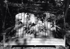 Backyard swing with shadows of leaves Stock Image