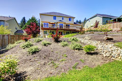 Backyard of two story house with fenced yard. Royalty Free Stock Image