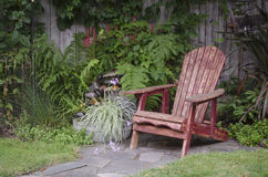 Backyard Vacation. A weathered wood chair sits at the end of a stone walkway Stock Photo