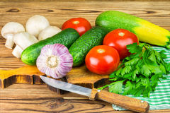 Backyard vegetables, tomatoes, cucumber, garlic, mushrooms, parsley on board, wooden background. Backyard vegetables, tomatoes, cucumber, garlic, mushrooms and Royalty Free Stock Images