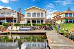 Backyard view from dock. Paneled two story house with glass balcony. Backyard view from dock Stock Images