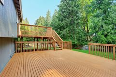 Backyard view of grey rambler house with upper and lower decks Royalty Free Stock Photo