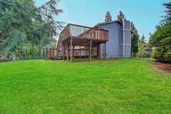 Backyard view of grey rambler house with upper and lower decks. And green lawn. Kirkland, WA, USA stock photos