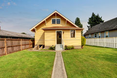 Backyard view of yellow siding craftsman house. Royalty Free Stock Images