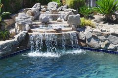 Backyard waterfall. Backyard swimming pool with waterfall Royalty Free Stock Photography