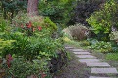 Backyard Woodland Path. A tiled garden path curves through a wooded backyard garden Stock Photography