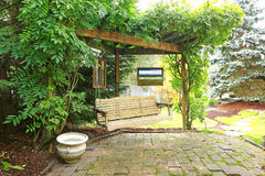 Backyrd rest area with hanging bench. Summer backyard garden with rest area. View of wooden hangin bench and brich floor Stock Photos