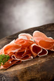 Bacon. Photo of delicious sliced bacon on wooden table with parsley Stock Photo