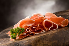 Bacon. Photo of delicious sliced bacon on wooden table with parsley Royalty Free Stock Photo