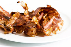 Bacon. Fried bacon served on white plate Royalty Free Stock Photo