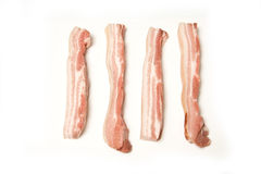 Bacon. Four strips of uncooked bacon isolated against a white background Stock Photos