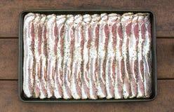Bacon affettato crudo del granello di pepe in strato di cottura Fotografia Stock