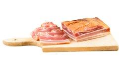 Bacon affumicato crudo su un piatto di legno immagini stock